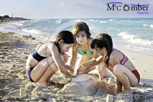 Three girls building a sand castle stock photograph