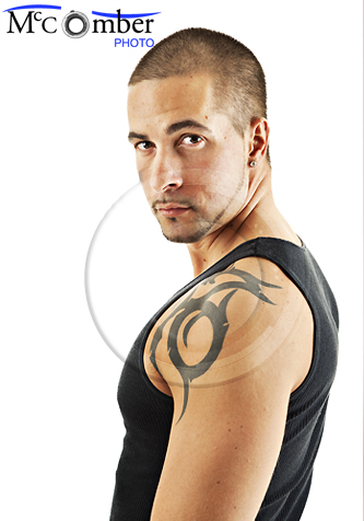 Muscular tattooed young man looking over his shoulder