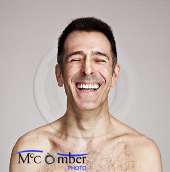 Shirtless man bursting with laughter
