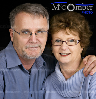 Happy elderly couple on black background