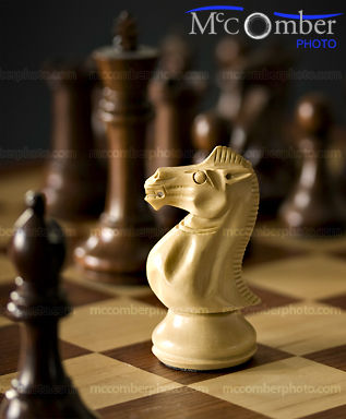 White Knight amongst Black Chess Pieces