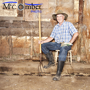 Stock photo: Senior farmer posing in old barn