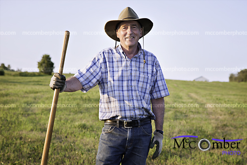 Happy senior farmer in a field