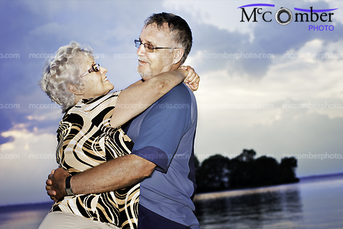 Senior couple dancing by lake at sunset