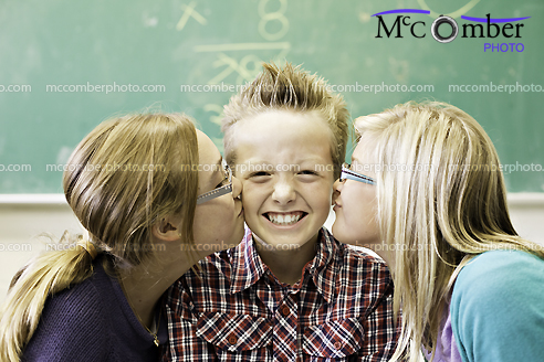 Cute Kid smiles while being kissed by two girls
