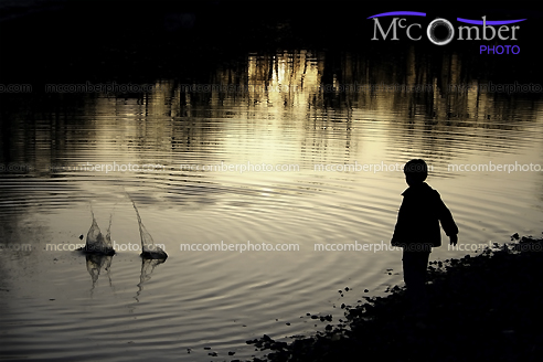 Boy silhouette throwing rocks in water
