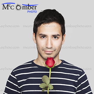 Young Hopeful Hispanic Man Offers a Red Rose