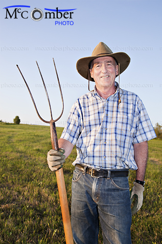 Stock Photo: Proud senior farmer in his field vertical