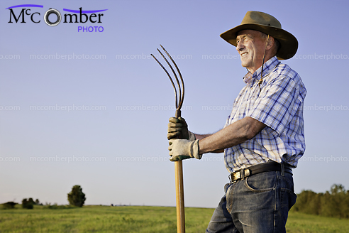 Stock photo: Senior farmer overlooking his field at the golden hour