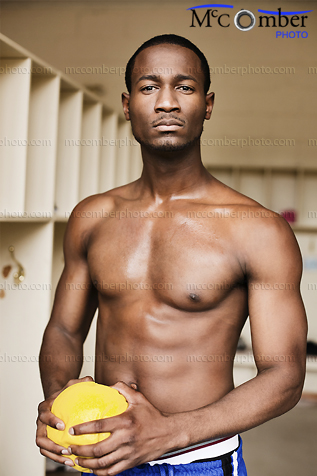 Stock Photo: Black Athlete in Locker Room with Yellow Handball