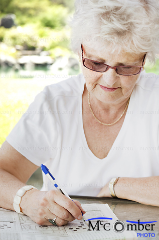 Stock Photo: Senior Woman does newspaper crossword puzzle in park
