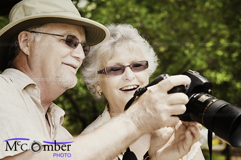 Stock Photo: Senior couple looking at the back of DLSR camera with delight