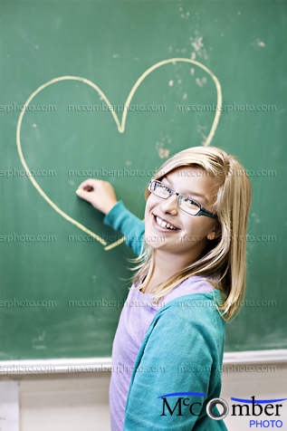 Featured Stock Photograph - School Girl Draws a Heart On black board
