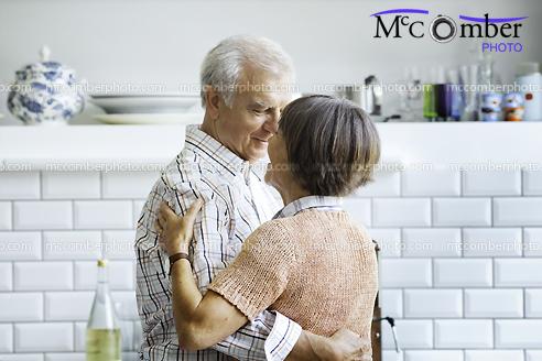 Stock Photograph - Senior couple dancing in kitchen