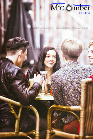 stock photo - Four friends at a cafe vertical