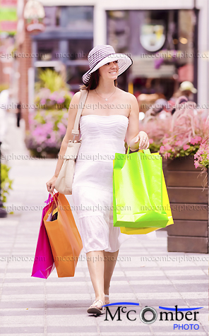 Stock Photograph - Woman shopping downtown in Summer dress