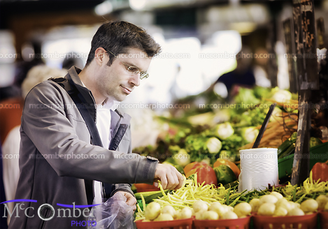 Stock Photograph - Handsome single man buying vegetables at farmers market