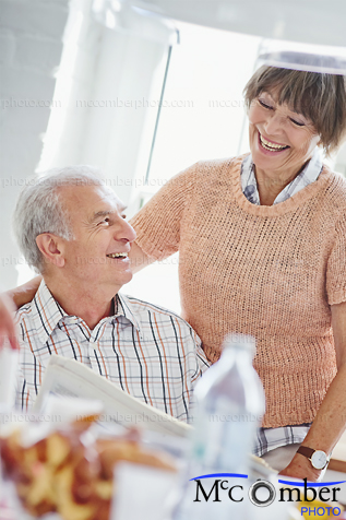 Stock Photograph - Elderly couple laughing at a newspaper article