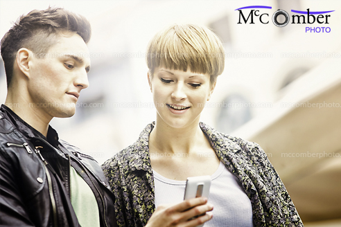 Stock Photograph - Two friends texting in Urban Setting