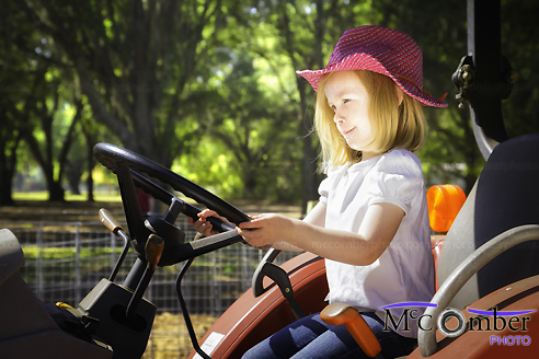 Stock Photo: Little Girl at the Wheel of Huge Tractor