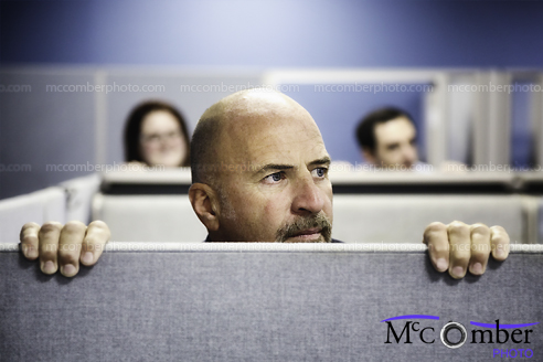 Stock Photo - Bald man emerging from cubicle
