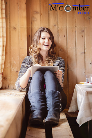 Stock Photo - Swiss teenager smiling in chalet with digital tablet
