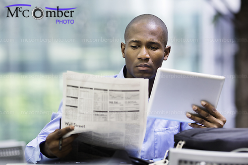 Stock Photo - Businessman compares quotes between newspaper and tablet