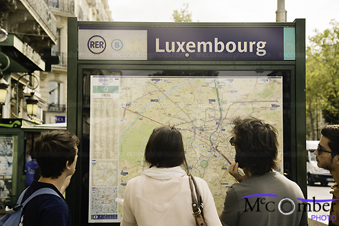 Stock Image - Tourists looking at Paris map on a metro station