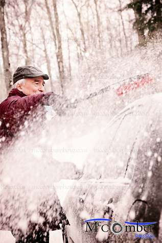 Stock Image - Senior man brushing snow off his car