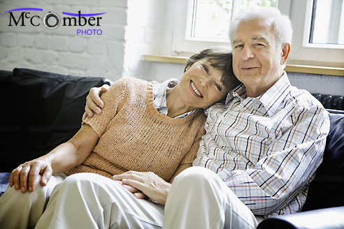 Amorous senior couple embracing on couch