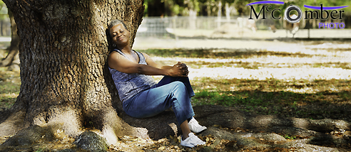 Senior black woman relaxing by a tree