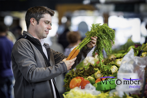 Stock Image: Young man buying organic vegetables at local market