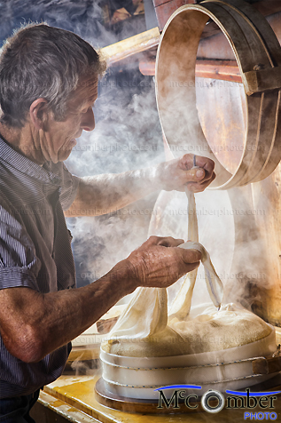 Stock Image: Senior Swiss Farmer making cheese