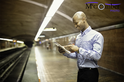 Stock Image: Bald man using digital tablet while waiting for subway