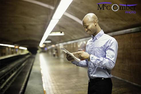 Stock Image: Bald man using digital tablet while waiting for subway