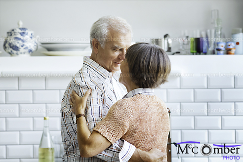 Stock Image: Elderly couple slow dancing in kitchen